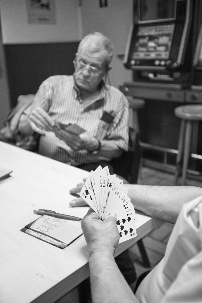 Men play rummy in the back of the shop. Duesseldorf, Germany, 2018.