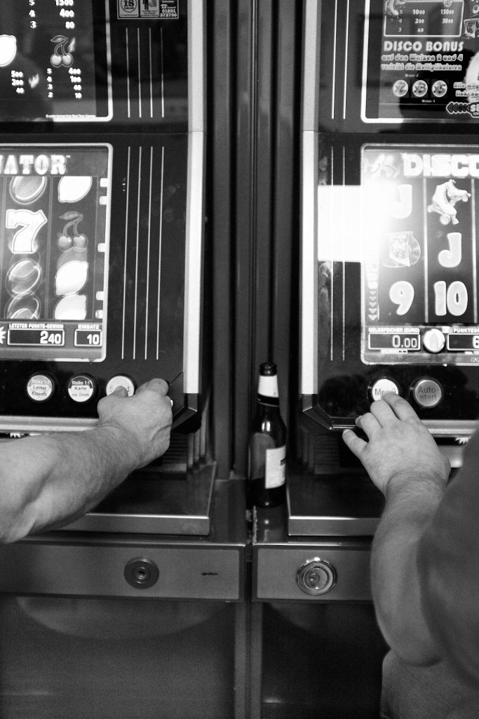 Two men try their luck on the slot machine. Duesseldorf, Germany, 2018.
