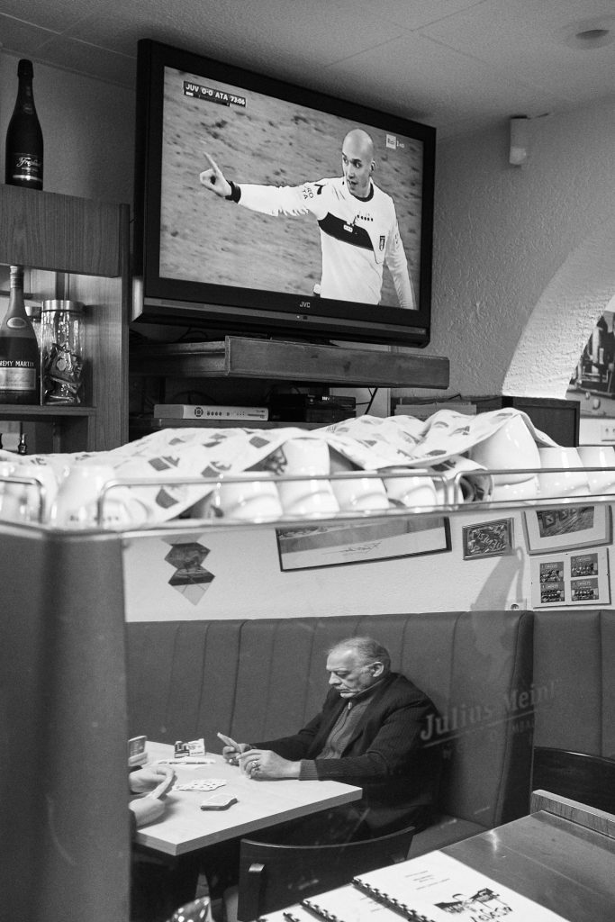A man playing cards is reflected in a coffee machine while a football match goes on on TV. Duesseldorf, Germany, 2018.