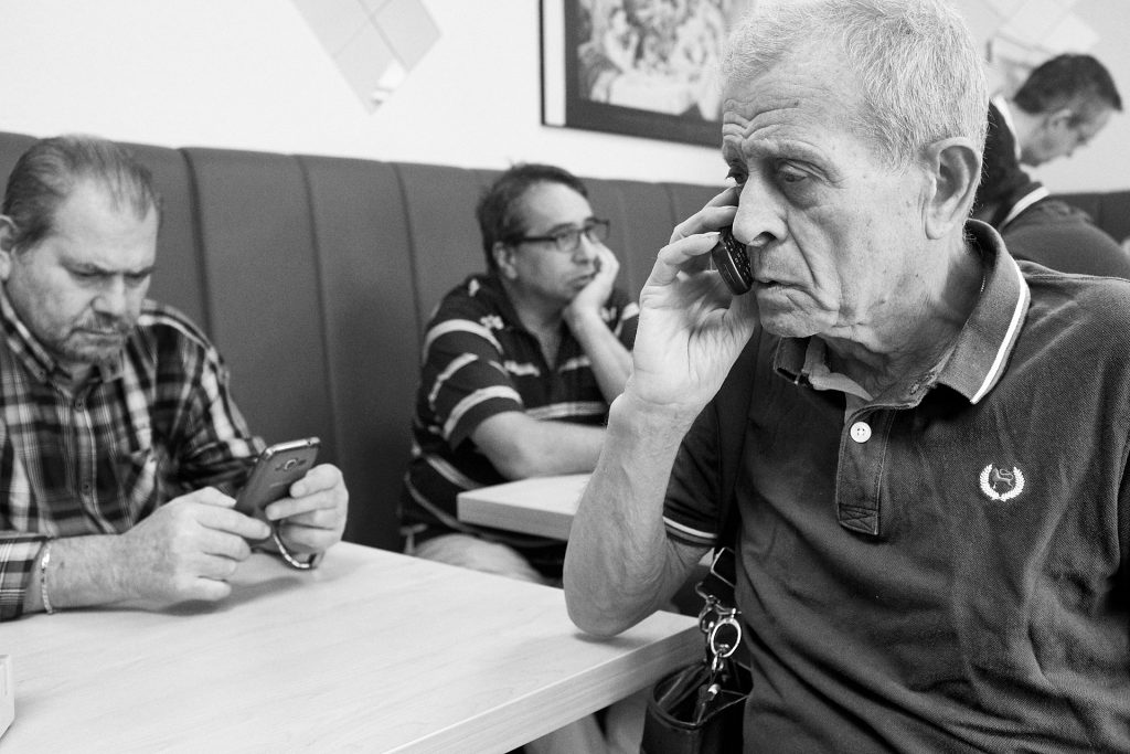 A man makes an international call on the telephone to consult his lawyer about his inheritance. Duesseldorf, Germany, 2018.